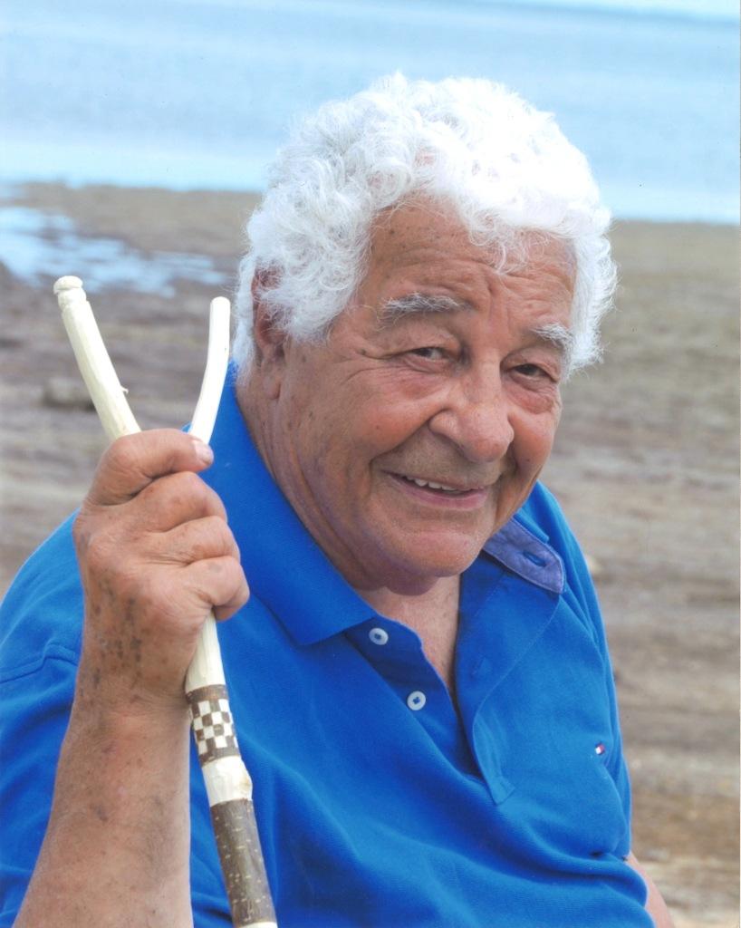 Antonio Carluccio on an Australian beach holding a wooden foraging stick