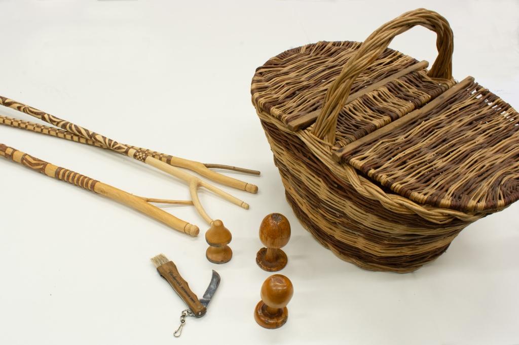 Carved hazel sticks with a wicker lidded mushroom basket, knife and wooden mushrooms